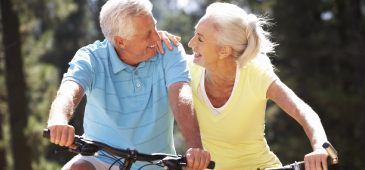 An old couple on bikes smiling