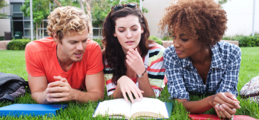 College students laying in the grass looking at a book